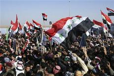 Iraqi Sunni Muslims wave the old flag of Iraq during an anti-government demonstration in Ramadi, 100 km (62 miles) west of Baghdad, December 26, 2012. Tens of thousands of Sunni Muslims blocked Iraq's main trade route to neighbouring Syria and Jordan in a fourth day of demonstrations on Wednesday against Shi'ite Prime Minister Nuri al-Maliki. REUTERS/Stringer (IRAQ - Tags: POLITICS CIVIL UNREST)