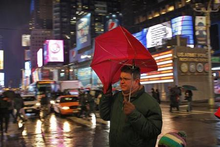 A man tries to control his umbrella as he takes cover from the rain in a winter storm at Times Square in New York, December 26, 2012. The severe winter weather that hit parts of the central and southern United States on Christmas Day moved eastward on Wednesday, causing flight delays and dangerous road conditions in the Northeast and Ohio Valley. REUTERS/Eduardo Munoz (UNITED STATES - Tags: ENVIRONMENT)