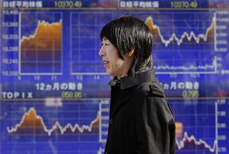 A pedestrian passes an electronic monitor displaying graphs of stock indices outside a brokerage in Tokyo December 27, 2012. The Nikkei share average climbed 1.4 percent to a 21-month high on Thursday, led by exporters, as the new Japanese prime minister's vow to battle deflation and a strong currency weighed on the yen. REUTERS/Yuriko Nakao (JAPAN - Tags: BUSINESS)