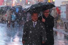 Una potente tormenta invernal obligó el jueves a la cancelación de unos 200 vuelos de Estados Unidos, entorpeciendo los viajes de fin de año mientras fuertes nevadas y vientos azotan el noreste de Estados Unidos. En la imagen, dos personas caminan por Times Square, Nueva York, con un paraguas mientras cae la nieve, el 26 de diciembre de 2012. REUTERS/Eduardo Muñoz