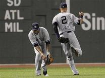 New York Yankees right fielder Andruw Jones (L) bobbles a ball hit by Boston Red Sox's Dustin Pedroia (not pictured) after Yankees teammate Derek Jeter (R) dropped it during the first inning of American League MLB baseball action at Fenway Park in Boston, Massachusetts September 11, 2012. REUTERS/Jessica Rinaldi