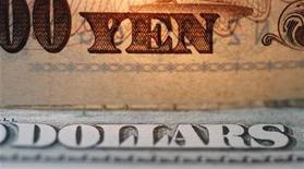 """Слова """"иена"""" и """"доллары"""" на банкнотах в обменном пункте Interbank Inc. в Токио 9 сентября 2010 года. Курс иены к доллару снизился до минимума двух лет на фоне ожиданий, что новое правительство во главе с Синдзо Абэ поведет курс на ослабление национальной валюты. REUTERS/Yuriko Nakao"""