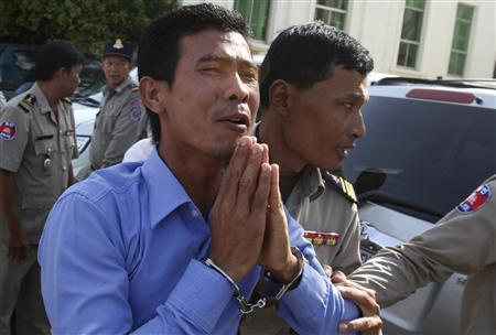Born Samnang (C) is escorted by police officers at the Appeals Court in central Phnom Penh December 27, 2012. REUTERS/Samrang Pring