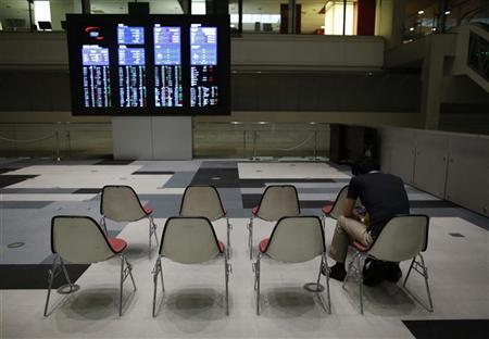 A visitor looks at his mobile phone in front of monitors displaying market indices at the Tokyo Stock Exchange in Tokyo July 13, 2012. REUTERS/Toru Hanai