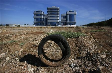 A tire is seen on a site set aside for future construction, next to office buildings in the Andalusian capital of Seville October 4, 2012. REUTERS/Marcelo del Pozo