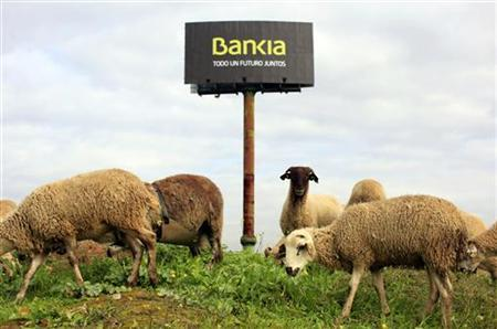 Sheep are seen next to a billboard of Spain's Bankia bank is seen on the outskirts in the Andalusian capital of Seville December 4, 2012. REUTERS/Marcelo del Pozo