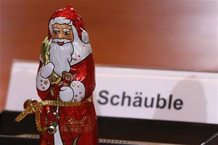 A chocolate Santa Claus, for the occasion of St. Nicholas Day, stands in front of the name place card for German Finance Minister Wolfgang Schaeuble before the weekly cabinet meeting in Berlin December 6, 2012. REUTERS/Wolfgang Rattay