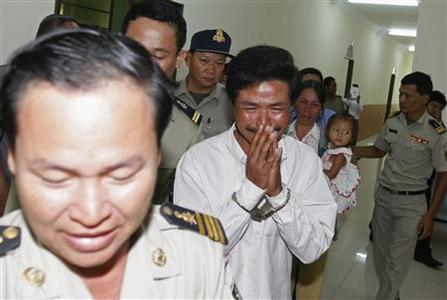 Sok Sam Oeun (C) is escorted by police officers as his wife and his daughter (center R) cry at the Appeal Court in central Phnom Penh December 27, 2012. REUTERS/Samrang Pring