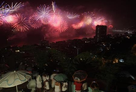 People watch fireworks exploding above Copacabana beach during New Year celebrations in Babilonia slum in Rio de Janeiro January 1, 2012. REUTERS/Ricardo Moraes