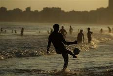A man kicks a ball at the Copacabana beach in Rio de Janeiro December 25, 2012. REUTERS/Pilar Olivares