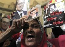 """El derrocado presidente egipcio Hosni Mubarak va a ser trasladado de la clínica en la que permanece detenido en prisión a un hospital militar, dijeron el jueves fuentes de seguridad y medios estatales. Imagen de una manifestación en apoyo de Mubarak en el exterior del Tribunal Superior de El Cairo el 23 de diciembre. El cartel de la derecha dice """"Mubarak está oprimido, Mubarak es inocente, Mubarak es un luchador honorable"""". REUTERS/Mohamed Abd El Ghany"""