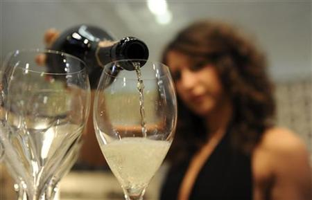 A woman fills glasses with sparkling wine at the Vinitaly wine expo in Verona April 8, 2010. REUTERS/Paolo Bona/Files