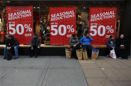 Shoppers rest outside a clothing shop during the Boxing Day sales on Oxford Street in central London, December 26, 2012. REUTERS/Andrew Winning