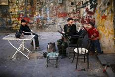 A Free Syrian Army fighter jokes with a child in the old city of Aleppo December 27, 2012. REUTERS/Ahmed Jadallah