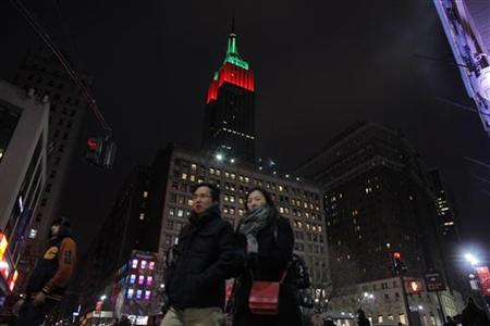 People walk near The Empire State Building as it is lit up in red and green on Christmas day in New York December 25, 2012. REUTERS/Eduardo Munoz