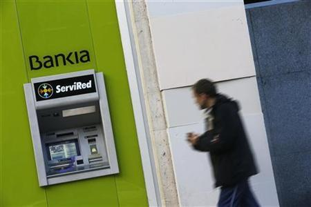 A man walks past an automated teller machine of Spain's nationalized lender Bankia in Madrid November 28, 2012. REUTERS/Susana Vera