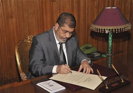 Egypt's President Mohamed Mursi signs a decree to put into effect the new constitution in Cairo December 25, 2012, in this handout photo released by Egyptian Presidency office. REUTERS/Egyptian Presidency/Handout