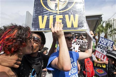 Two male protestors kiss next to a member of the Westboro Baptist Church outside the Republican National Convention in Tampa, Florida August 28, 2012. REUTERS/Philip Andrews