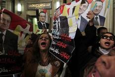 Un grupo de partidarios del derrocado mandatario egipcio Hosni Mubarak sostienen una serie de afiches con su imagen en la Corte Suprema de El Cairo, dic 23 2012. El fiscal público de Egipto ordenó que el derrocado presidente Hosni Mubarak sea trasladado de la clínica en la que permanece detenido a un hospital militar en base a recomendaciones de un informe médico, dijeron el jueves fuerzas de seguridad. REUTERS/Mohamed Abd El Ghany