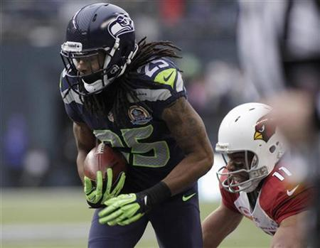 Seattle Seahawks' Richard Sherman (25) intercepts a pass meant for Arizona Cardinals' Larry Fitzgerald (11), returning it for a touchdown during the second quarter of their NFL football game in Seattle, Washington, December 9, 2012. REUTERS/Robert Sorbo