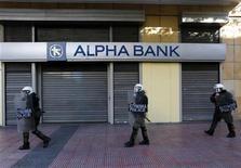 El banco central de Grecia dijo que los cuatro principales bancos del país necesitan 27.500 millones de euros de capital para recuperar sus coeficientes de solvencia, confirmando las revelaciones de los prestamistas la semana pasada. Imagen del 6 de diciembre de unos antidisturbios griegos ante una sucursal cerrada del banco Alpha en la plaza Syntagma de Atenas. REUTERS/Yannis Behrakis