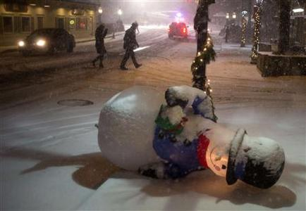 A inflatable snow man is seen fallen along a sidewalk as well-wishers cross the street to visit a memorial in Sandy Hook Village, the site of the December 14 school shooting, in Newtown, Connecticut on December 26, 2012. REUTERS/Adrees Latif