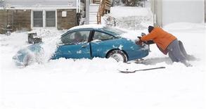 Pessoas ajudam a empurrar um carro preso na neve em Cedar Falls, nos EUA. Uma tempestade de inverno potente, responsável por ventos, neve, tornados e acidentes de trânsito, atingiu o nordeste dos Estados Unidos nesta quinta-feira, cancelando centenas de voos, mas também revivendo o que vinha sendo uma temporada de esqui sem neve. 20/12/2012 REUTERS/Matthew Putney/The Waterloo Courier/Handout