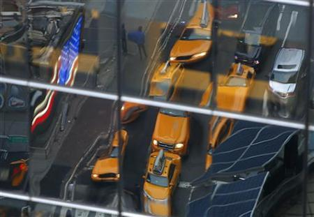 Taxis are reflected in a window in Times Square in New York December 17, 2012 REUTERS/Carlo Allegri