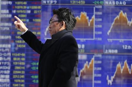 A man points up as he passes an electronic monitor displaying market indices outside a brokerage in Tokyo December 27, 2012. REUTERS/Yuriko Nakao