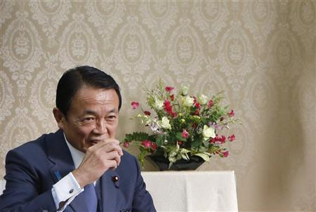 Japan's new Finance Minister Taro Aso sips green tea before signing a document to mark the transfer of duties from former Finance Minister Koriki Jojima (not pictured) at the Finance Ministry in Tokyo December 27, 2012. REUTERS/Yuriko Nakao