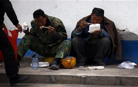 Migrant workers eat their lunch on a footpath outside a construction site in central Beijing April 2, 2012. REUTERS/David Gray/Files