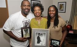 Filmmaker Byron Hurt is pictured with his mother, Frances Hurt, and sister, Taundra Hurt, holding family photos of Hurt's father, Jackie Hurt, who died in 2007 at age 64 as a result of pancreatic cancer in this undated handout photo obtained by Reuters December 21, 2012. REUTERS/Bryon Hurt/Handout