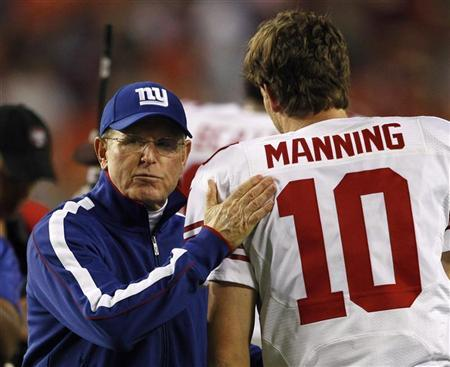 New York Giants head coach Tom Coughlin (L) wishes his starting quarterback Eli Manning (R) good luck prior to their NFL football game against the Washington Redskins in Landover, Maryland December 3, 2012. REUTERS/Gary Cameron