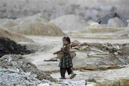 A girl walks at a waste dump near a copper mine in Sarlingyi township December 14, 2012. Picture taken December 14, 2012. REUTERS/Soe Zeya Tun