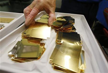 An employee holds an unpressed gold Combibar at a plant of gold refiner and bar manufacturer Valcambi SA in the southern Swiss town of Balerna December 20, 2012. REUTERS/Michael Buholzer