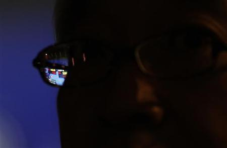 A stock index board is seen through a pair of glasses of a pedestrian outside a brokerage in Tokyo November 22, 2012. REUTERS/Kim Kyung-Hoon/Files