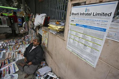 An advertisement for Bharti Infratel Limited's initial public offering (IPO) is seen posted on a wall as a roadside vendor selling magazines and newspapers waits for customers in New Delhi December 12, 2012. REUTERS/Adnan Abidi