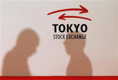 Visitors cast their shadows on the logo of the Tokyo Stock Exchange, prior to a ceremony marking the end of trading in 2012 at the Tokyo Stock Exchange in Tokyo December 28, 2012. Japan's Nikkei average rose to a 21-month high on Friday, posting its best yearly gain since 2005 on the last trading day of the year as exporters were buoyed by a weaker yen on expectations of aggressive monetary stimulus under Japan's new Prime Minister. REUTERS/Kim Kyung-Hoon (JAPAN - Tags: BUSINESS)