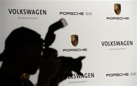 A photographer is silhouetted during a press conference of German carmakers Volkswagen and Porsche in Wolfsburg, July 5, 2012. REUTERS/Fabian Bimmer (GERMANY - Tags: BUSINESS TRANSPORT)