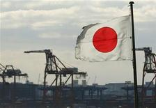 A Japanese flag flutters in front of a shipping container area, at a port in Tokyo December 19, 2012. REUTERS/Yuriko Nakao (JAPAN - Tags: MARITIME BUSINESS)