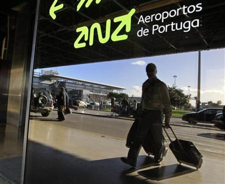 Passengers arriving at the departure hall are reflected in the glass at Lisbon's airport December 26, 2012. The Portuguese cabinet meeting on Thursday is likely to announce the winning bid for airports operator ANA in a privatization expected to raise up to 3 billion euros for the debt-ridden, bailed out state. Four binding bids by international consortia are led by France's Vinci, Germany's Fraport, Zurich airport operator Flughafen Zurich and Argentina's Corporacion America. REUTERS/Jose Manuel Ribeiro (PORTUGAL - Tags: POLITICS BUSINESS EMPLOYMENT TRANSPORT)