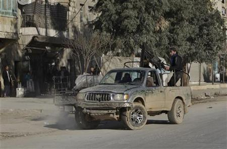 Free Syria Army fighters drive by in a car with an anti-aircraft gun in Aleppo city December 27, 2012. REUTERS/Ahmed Jadallah