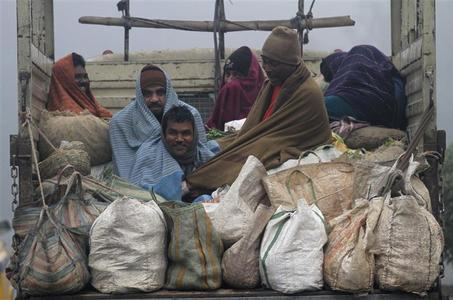 Vendors covered in blankets sit in the back of a supply truck after buying vegetables from a market on a cold winter morning in Kolkata December 28, 2012. REUTERS/Rupak De Chowdhuri