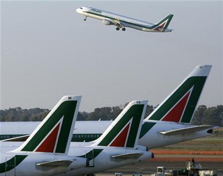 An Alitalia jet takes off over another three parked at Fiumicino airport in Rome December 23, 2008. REUTERS/Chris Helgren