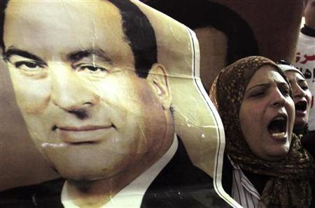 A supporter of ousted former Egyptian President Mohammed Hosni Mubarak stands near a poster of him at a protest outside a High Court in Cairo December 23, 2012. REUTERS/Mohamed Abd El Ghany