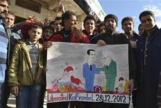 Demonstrators hold a placard during a protest against Syria's President Bashar al-Assad, after Friday prayers in Kafranbel near Idlib December 28, 2012. REUTERS/Raed Al-Fares/Shaam News Network/Handout