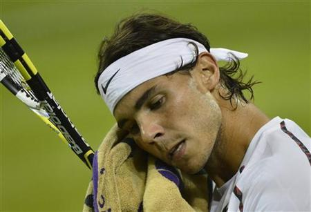 Rafael Nadal of Spain wipes his face in his men's singles tennis match against Lukas Rosol of the Czech Republic at the Wimbledon tennis championships in London June 28, 2012. REUTERS/Toby Melville/Files