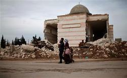 El líder de la oposición siria rechazó una invitación de Rusia para participar en negociaciones de paz, asestando un nuevo golpe a las esperanzas internacionales de poder resucitar la vía diplomática y poner fin a 21 meses de guerra civil. En la imagen, una familia pasa junto a una mezquita dañada en Azaz, en el norte de Alepo, el 28 de diciembre de 2012. REUTERS/Ahmed Jadallah