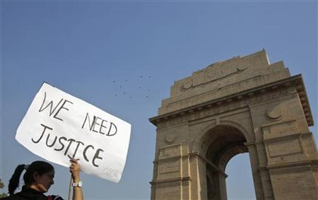A demonstrator holds a placard in front of the India Gate as she takes part in a protest rally organised by various women's organisations in New Delhi December 21, 2012. REUTERS/Adnan Abidi