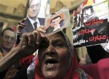 Una partidaria del derrocado mandatario egipcio Hosni Mubarak sostiene una fotografía con su imagen a las afueras de la Corte Suprema en El Cairo, dic 23 2012. Hosni Mubarak, el líder depuesto de Egipto que cumple con una condena de cadena perpetua por responsabilidad en la muerte de manifestantes durante una revuelta en 2011, permanecerá en un hospital militar por al menos dos semanas tras un deterioro de su salud, dijo el viernes su abogado. REUTERS/Mohamed Abd El Ghany